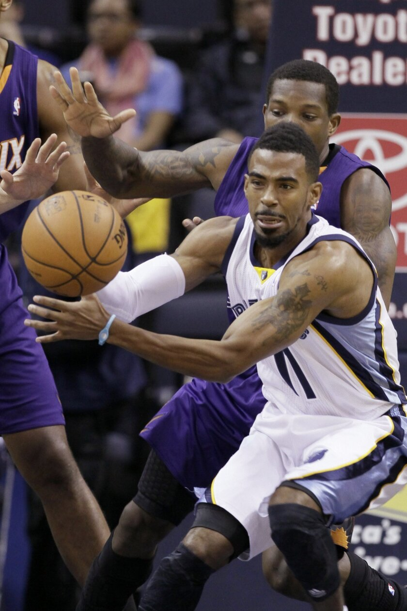 Memphis Grizzlies' Mike Conley (11) passes the ball in front of Phoenix Suns' Eric Bledsoe in the first half of an NBA basketball game in Memphis, Tenn., Tuesday, Dec. 3, 2013. (AP Photo/Danny Johnston)