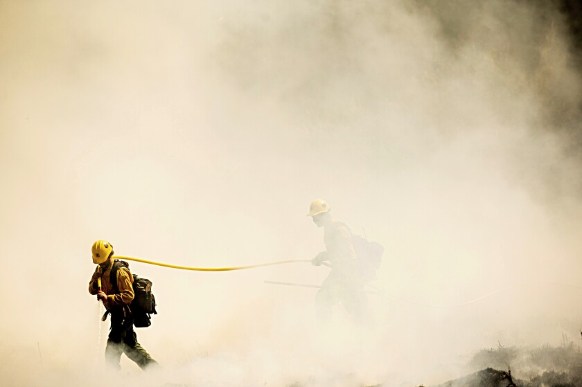 Two firefighters emerge from the smoke carrying a hose.
