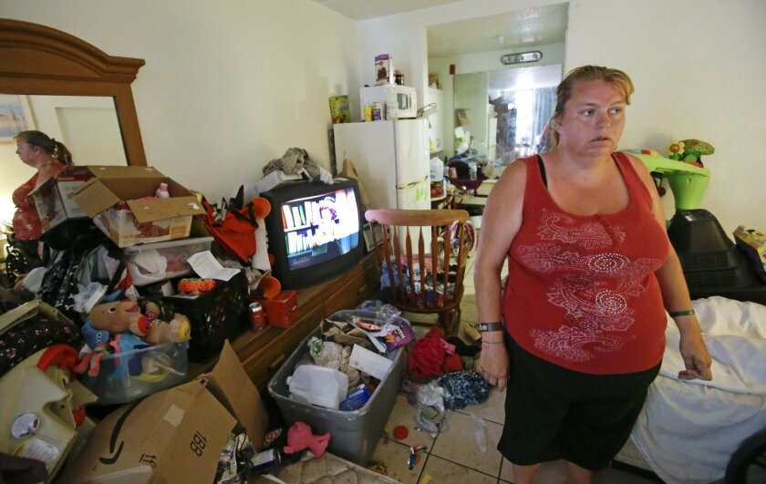 In this Tuesday, April 8, 2014 photo, Theresa Muller prepares to move out of her motel room she shares with her boyfriend, father and three children in Kissimmee, Fla.   Muller and her family have been homeless but plan to move to a home in a neighboring county. (AP Photo/John Raoux)
