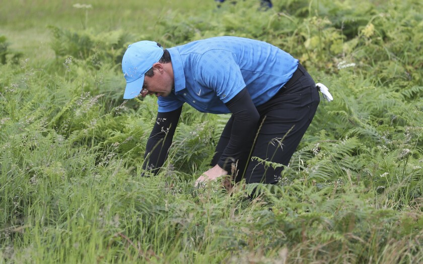 Northern Ireland's Rory McIlroy looks for his ball in the long rough on the 1st hole during the first round of the 148th Open Championship at Royal Portrush Golf Club in Northern Ireland.
