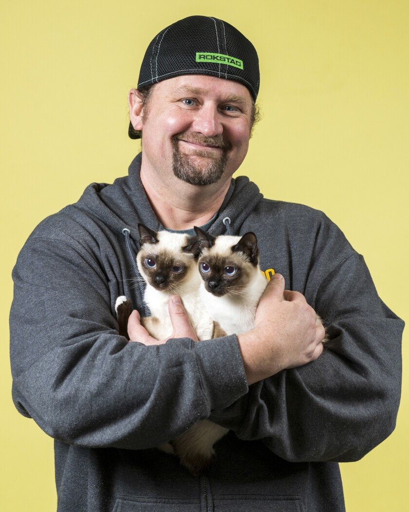 Aaron Prince holds his Toybob cats Tootsie, left, and Nokia.