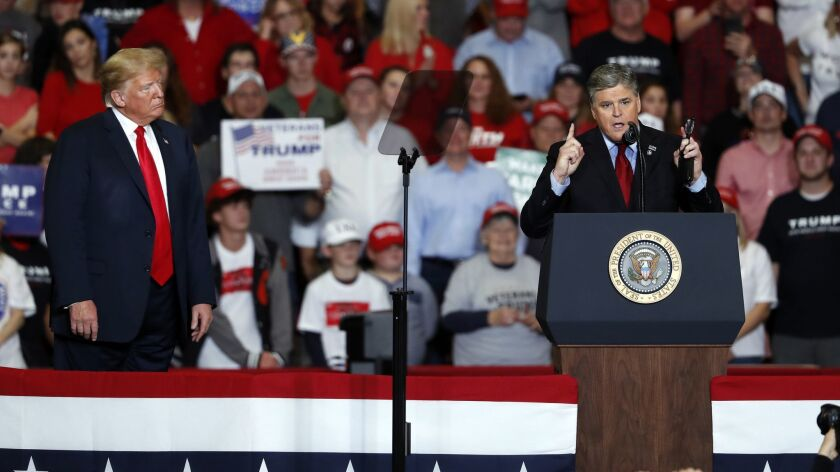 Television personality Sean Hannity, right, speaks as President Donald Trump listens during a campai