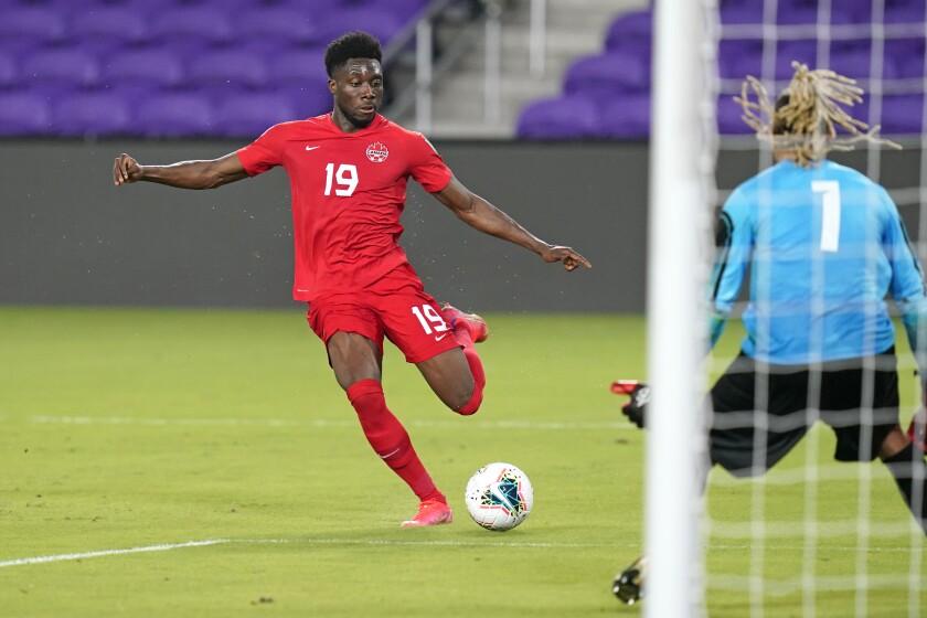Canada's Alphonso Davies takes a shot on goal against Bermuda goalkeeper Dale Eve.