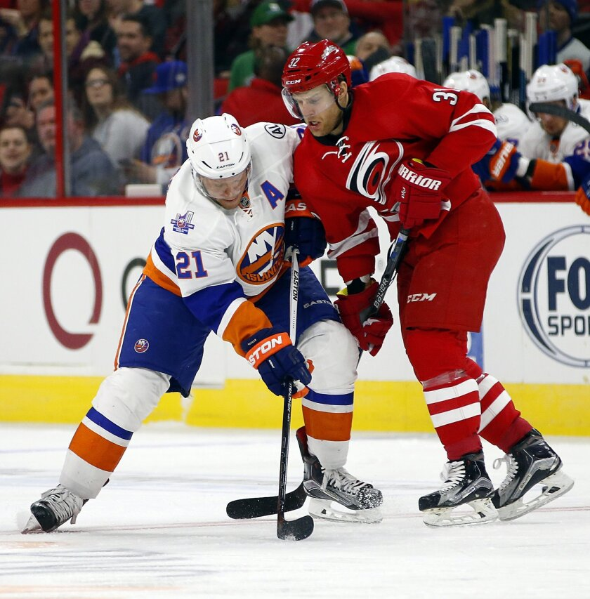 New York Islanders' Kyle Okposo (21) battles with Carolina Hurricanes' Kris Versteeg (32) during the first period of an NHL hockey game, Saturday, Feb. 13, 2016, in Raleigh, N.C. (AP Photo/Karl B DeBlaker)