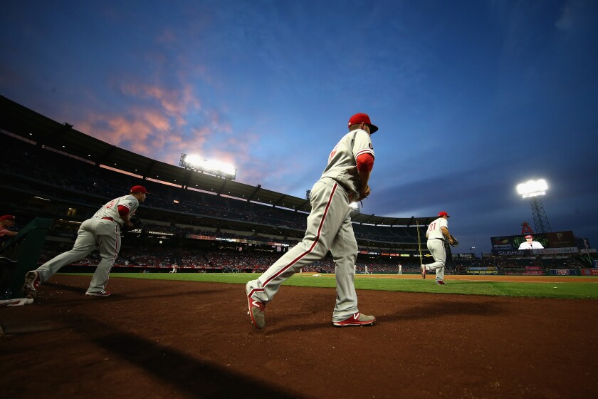 Phillies players run onto the field at Angel Stadium during a game in August 2017.