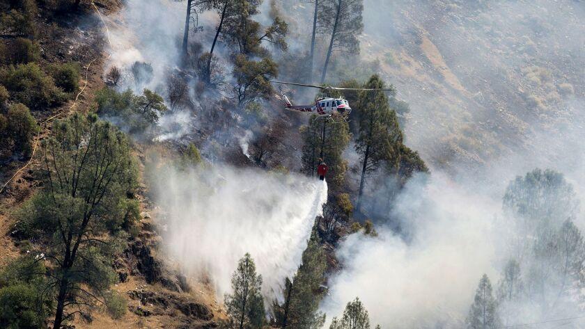 Crews battle the Ferguson Fire along steep terrain behind the Redbud Lodge along Highway 140 near El