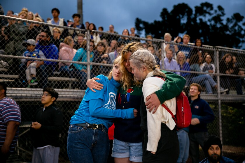 Poway High School students Lola Ethridge, Grace Jahnke and Jacqueline Van Tyne embrace one another at a vigil following the shooting at Chabad of Poway.