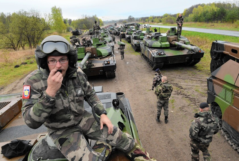 French soldiers unload tanks from a train in northern Poland. The troops and tanks are deployed for a NATO military exercise.
