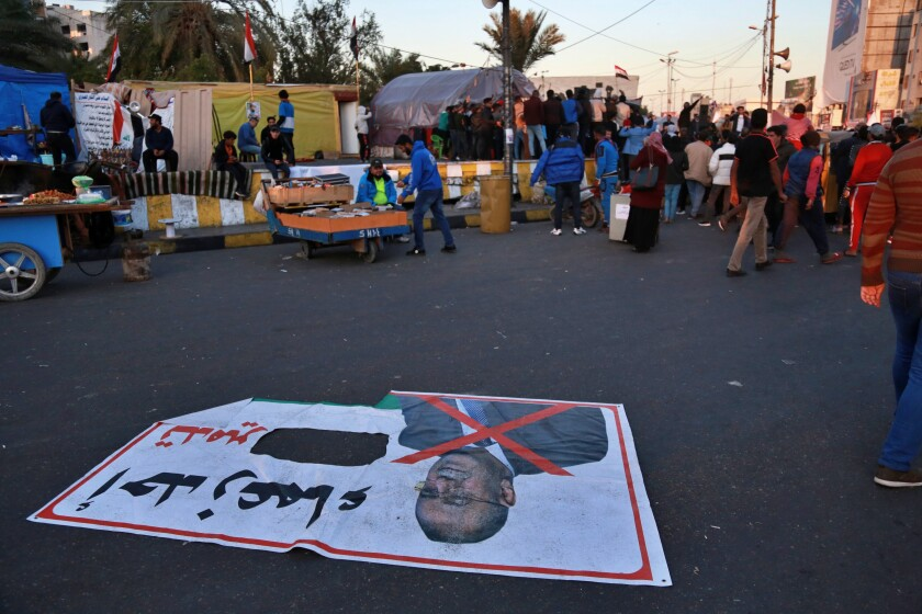 """In this Wednesday, Dec. 18, 2019 photo, a poster with a defaced photo of Qusay al-Suhail, a candidate for the prime minister's post, and Arabic that reads, """"one of the leaders of the destruction,"""" is lying on the ground in Tahrir Square, Baghdad, Iraq. Thousands of protesters poured into the streets of Baghdad and Iraq's southern provinces on Sunday, rejecting the nomination of what some call an Iran-backed candidate for the prime minister's post. The demonstrations came as a midnight deadline loomed without a solution being reached to name an interim premier. (AP Photo/Khalid Mohammed)"""