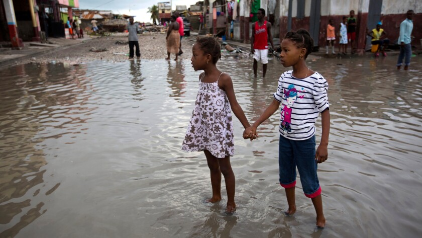 Girls help each other wade through a flooded street after the passing of Hurricane Matthew in Les Cayes, Haiti.