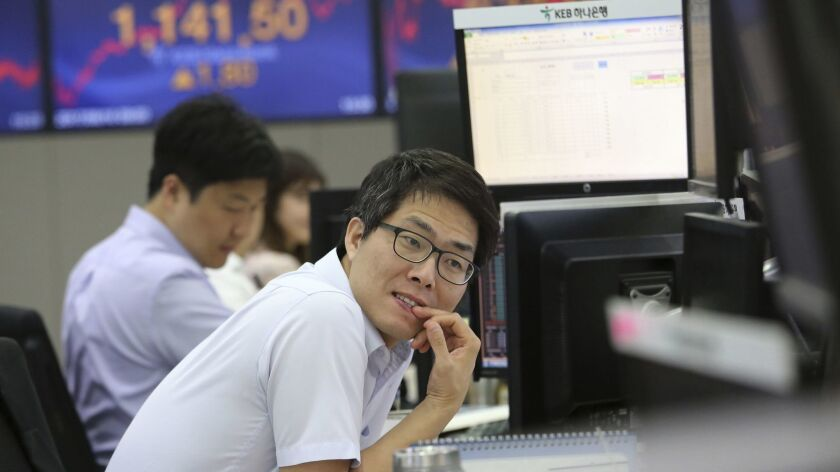 A currency trader watches monitors at the foreign exchange dealing room of the KEB Hana Bank headqua