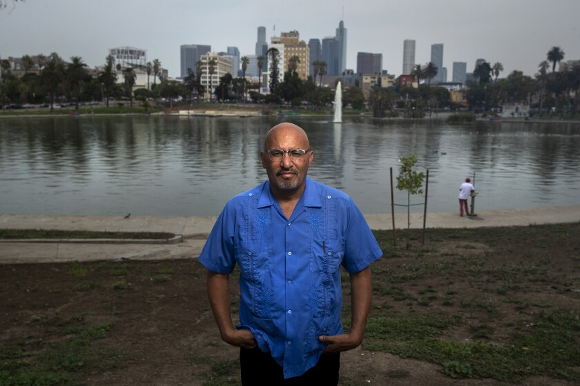 """LOS ANGELES, CA - AUGUST 21: Author Roberto Lovato is photographed at MacArthur Park in Los Angeles. He has a new book coming out about El Salvador titled, """"Unforgetting:A Memoir of Family, Migration, gangs, and Revolution in the Americas."""" (Mel Melcon / Los Angeles Times)"""