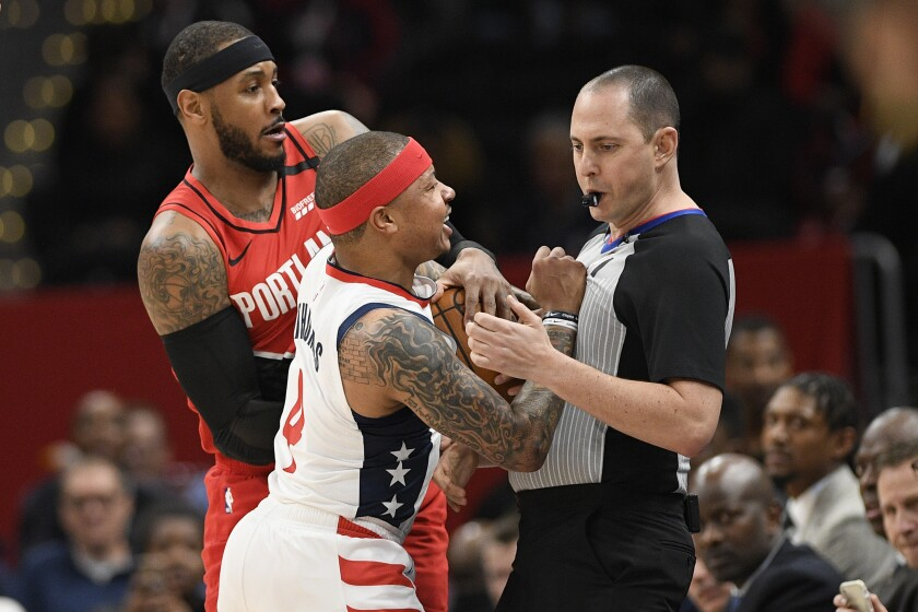 Washington Wizards guard Isaiah Thomas (4) comes in contact with referee Marat Kogut, right, next to Portland Trail Blazers forward Carmelo Anthony, back, during the first half of an NBA basketball game, Friday, Jan. 3, 2020, in Washington. Thomas was ejected from the game. (AP Photo/Nick Wass)