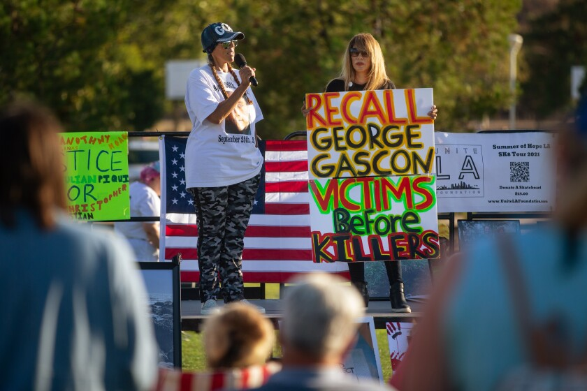 Two women on an outdoor stage, one with a sign that says Recall George Gascon; Victims before killers