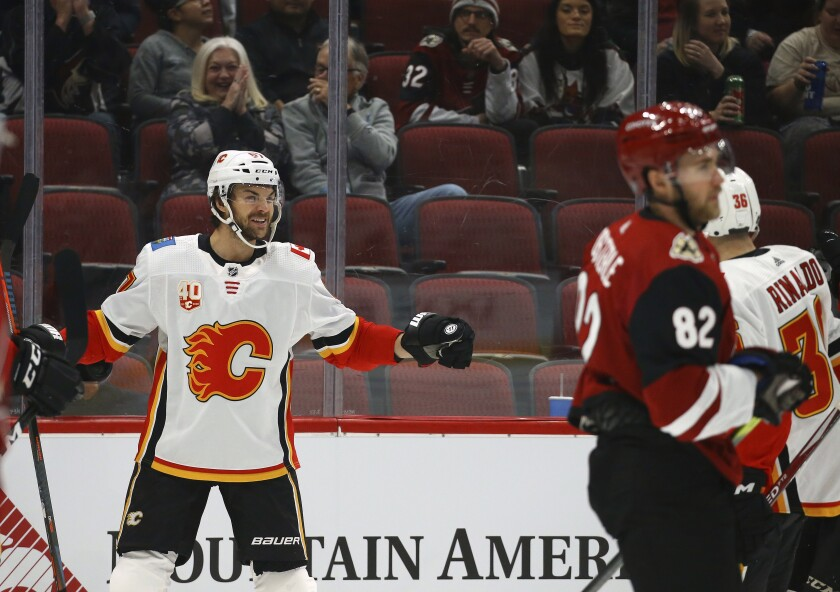 Calgary Flames right wing Michael Frolik, left, celebrates his goal with Flames center Zac Rinaldo (36) as Arizona Coyotes defenseman Jordan Oesterle (82) skates past during the first period of an NHL hockey game, Tuesday, Dec. 10, 2019 in Glendale, Ariz. (AP Photo/Ross D. Franklin)