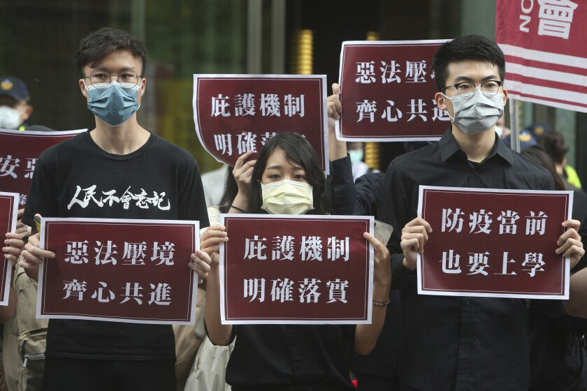 Hong Kong students and Taiwanese supporters hold signs of protest in Taiwan on May 28.