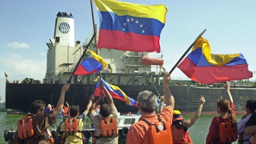 Trabajadores petroleros ondean banderas venezolanas durante su huelga en 2002 contra el entonces presidente Hugo Chávez. (Ana María Otero / Associated Press)
