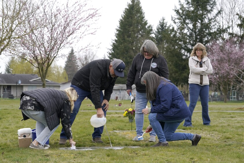 From front left, Wendy Jensen, Joe Woodmansee, Linda Holeman and Bonnie Dawson, the four children of Carole Rae Woodmansee, are joined by family friend Debbie Blazina, at right, Saturday, March 27, 2021, as they clean the headstone Carole shares with their father, Jim, who died in 2003, at Union Cemetery in Sedro-Woolley, Wash., north of Seattle, prior to a memorial service. Carole died a year ago on the same date in 2020, the day of her 81st birthday, from complications of COVID-19 after contracting it during a choir practice that sickened 53 people and killed two — a superspreader event that would become one of the most pivotal transmission episodes in understanding the virus. (AP Photo/Ted S. Warren)