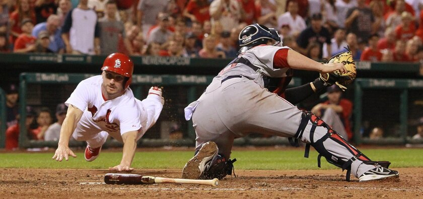 St. Louis Cardinals' Shane Robinson, left, scores past Boston Red Sox catcher Christian Vazquez during the seventh inning of a baseball game Tuesday, Aug. 5, 2014, in St. Louis. (AP Photo/St. Louis Post-Dispatch, Chris Lee)