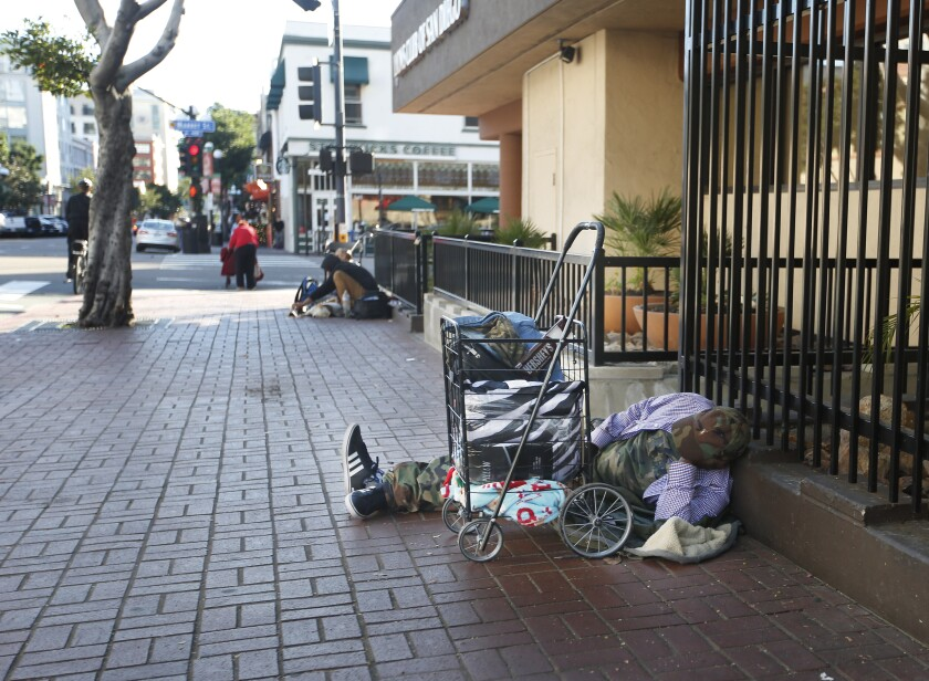 An apparently  homeless man sleeps on the sidewalk in downtown San Diego in this 2019 file photo.