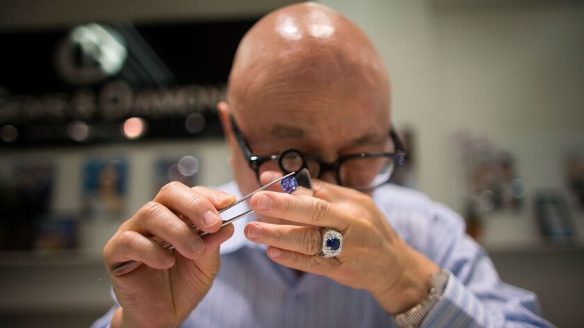 Jerry Young inspects a blue sapphire at Inta Gems & Diamonds. His store is the first owned by Cambodians in downtown L.A.'s Jewelry District.