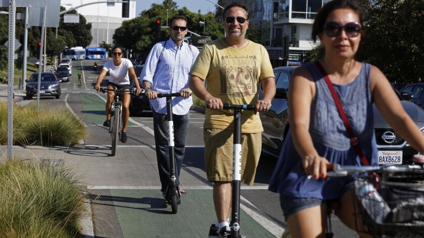 People ride Bird scooters alongside bicycles in Santa Monica in August.