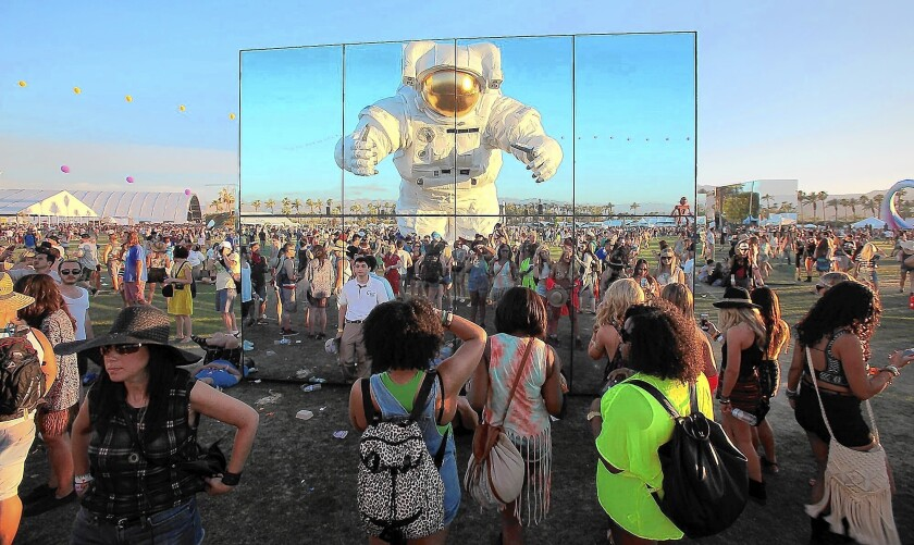 """A nearly 40-foot-tall astronaut """"Escape Velocity"""" by Poetic Kinetics, an L.A.-based art collective, is reflected in """"Reflection Fields"""" by Phillip K. Smith as it roams through the crowd at the Coachella Valley Music and Arts Festival April 11, 2014, in Indio."""