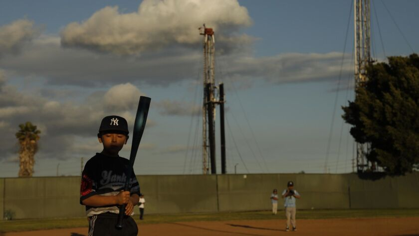 Benny Escobar, 7, stands at bat with two oil rigs towering in the background at John Mendez Baseball Park in Los Angeles' Wilmington neighborhood on April 16. Environmental groups are urging Gov. Gavin Newsom to ban fracking and to stop issuing new state permits for oil wells.