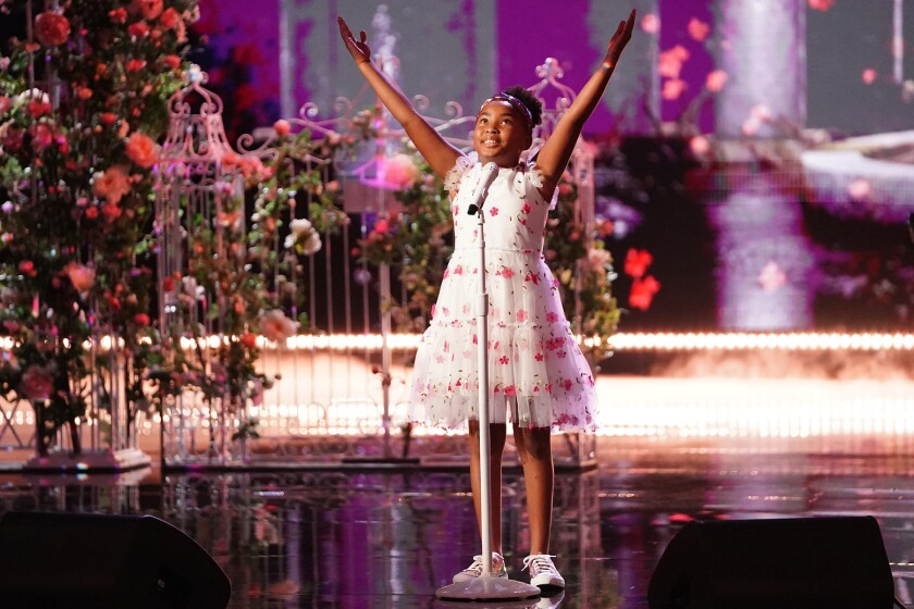 A young girl wearing a white floral dress with her arms stretched upward stands in front of a microphone.