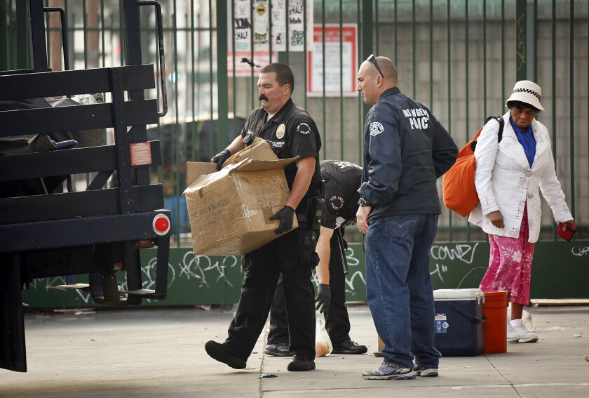 Officers remove a homeless person's belongings last week in downtown Los Angeles' skid row. On Wednesday, the L.A. City Council approved a measure limiting how much property homeless people can keep with them on the streets.