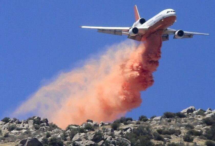 A DC-10 drops fire retardant ahead of the fire line on the mountains and ridges above Snow Creek Village near Cabazon as the Silver fire burns on in Riverside County.