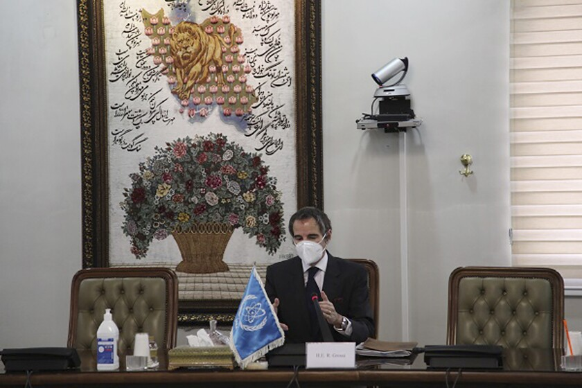 Rafael Mariano Grossi, in surgical mask and seated at a table, gestures as he speaks.