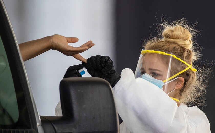 Healthcare workers tend to a driver in line at a drive-through Coronavirus (COVID-19) testing site at the Westminster Mall in Westminster, CA, Wednesday, April 8, 2020. The site is run by Elevated Health and is doing nasal testing for $125 and antibody testing for $75.