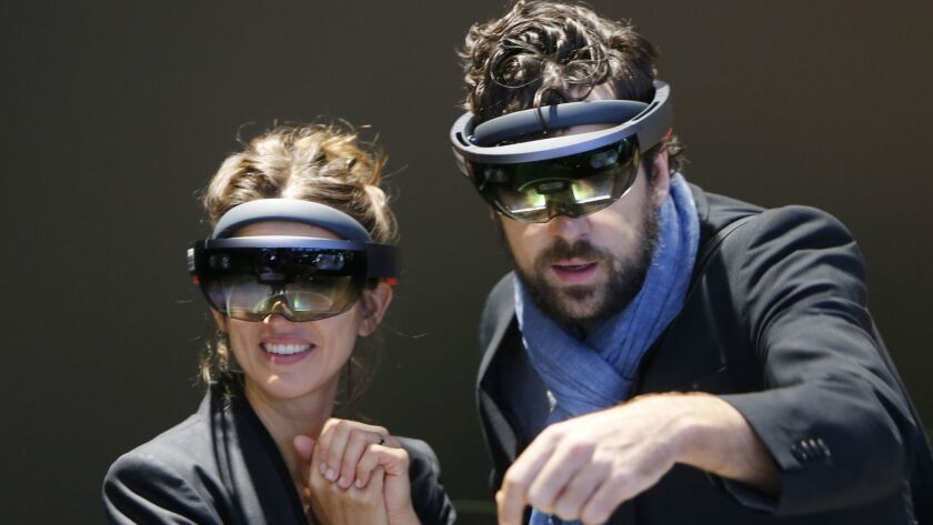 FILE- In this Sept. 24, 2017, file photo people use Microsoft Hololens to get an impression of Merce