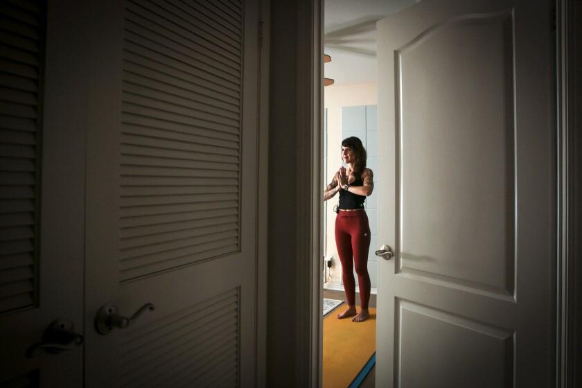 Laura Schwartz, seen through an open door, practices yoga on a yellow mat.
