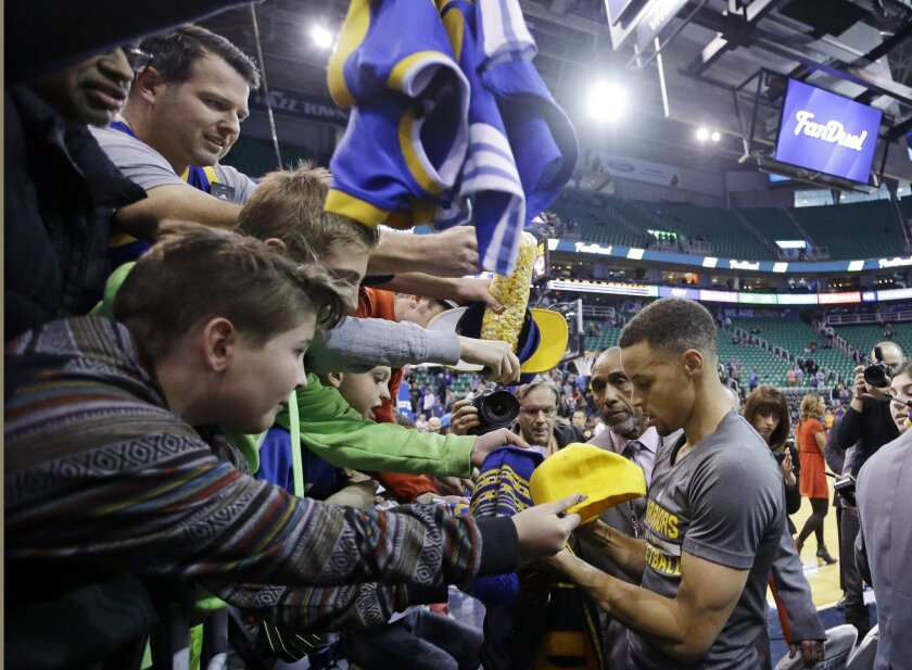 Golden State Warriors guard Stephen Curry, right, signs autographs before the start of their game with the Utah Jazz during an NBA basketball game Wednesday, March 30, 2016, in Salt Lake City. (AP Photo/Rick Bowmer)