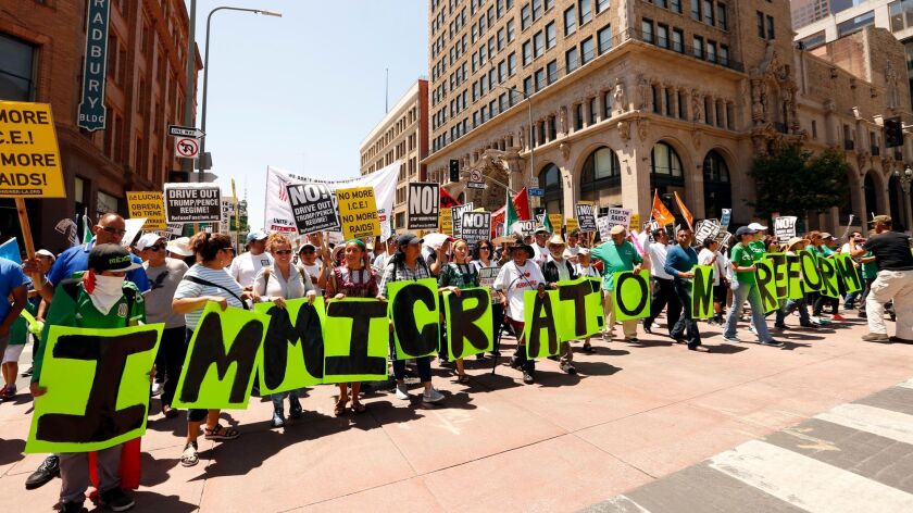 "Marchers carry letters spelling out ""Immigration reform now"" while marching down Broadway during the"