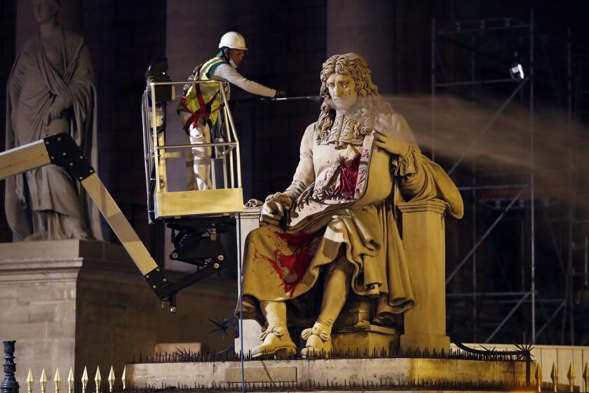 Un empleado del Ayuntamiento de París limpia la estatua de Jean-Baptiste Colbert, un ministro real del siglo XVII que escribió las reglas que gobernaban a los esclavos en las colonias de Francia, en París el martes 23 de junio de 2020. (AP Foto/Thibault Camus)