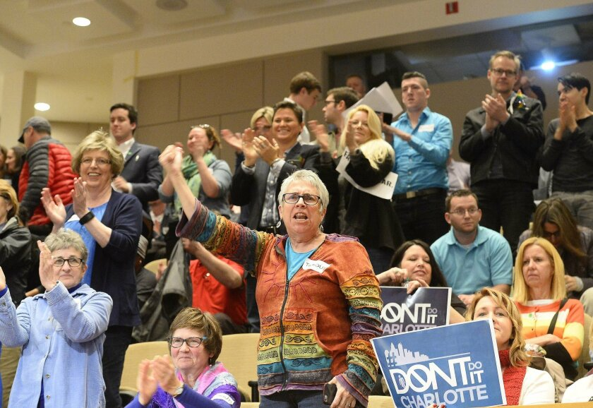 In this photo taken on Monday, Feb. 22, 2016, members of the audience cheer a City Council meeting's vote on a nondiscrimination ordinance, in Charlotte, N.C. The Charlotte City Council approved LGBT protections in a 7-4 vote Monday night. North Carolina's largest city has legalized the ability of transgender people to choose public restrooms corresponding to their gender identity. The governor calls it a threat to public safety, and some state lawmakers are vowing to overrule the city. (Robert Lahser /The Charlotte Observer via AP)