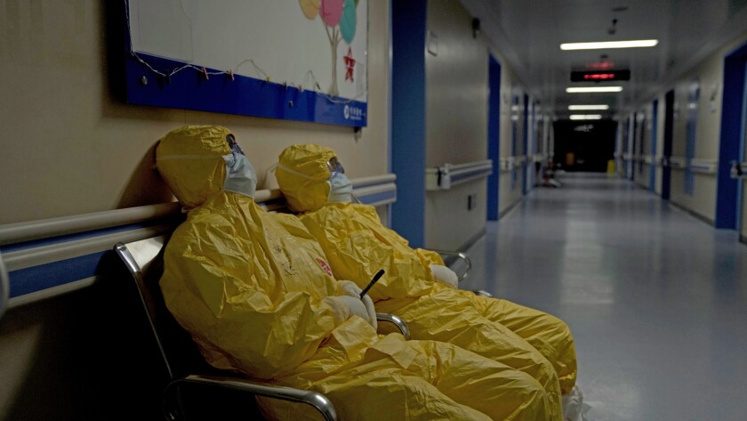 "Exhausted hospital workers garbed in PPE in the documentary ""76 Days."""