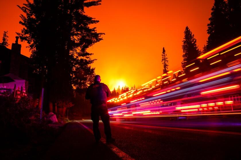 A vehicle streaks by in a long exposure as Fresno County Sheriff's Deputy Jeffery Shipman stands along State Route 168