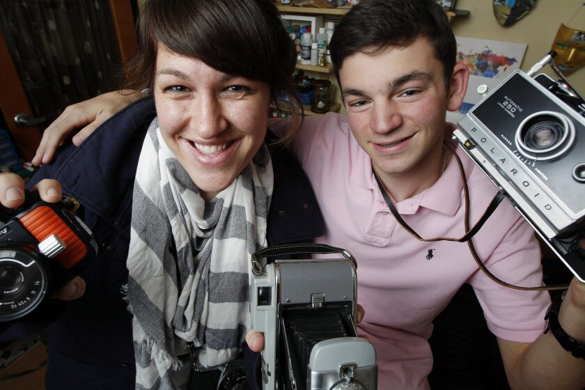 Photography teacher Irish Grzanich (left) and 8th grader Louis Eisenberg, 14, hold up some film cameras students have access to in their photography classes at Fusion Academy on Wednesday in San Diego, California. The two have published a photo book called Tikkun Olam: Repairing the World.