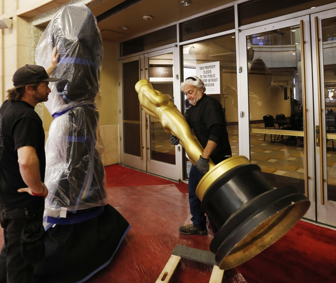 Worker Frank Rose lifts an Oscar statue into the Dolby Theatre during rehearsals for the 91st Oscars show Sunday.