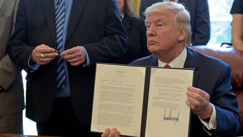 President Trump shows off the executive memorandum on an investigation of steel imports after signing it.