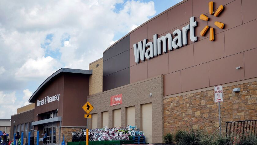 FILE - In an Aug. 26, 2016 file photo, people walk in and out of a Walmart store, in Dallas. Walmar