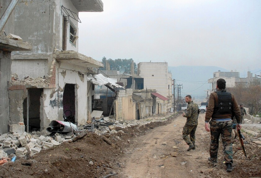 Syrian government forces patrol a street in the western town of Zara, near the Lebanese border, which had long been in rebel hands.