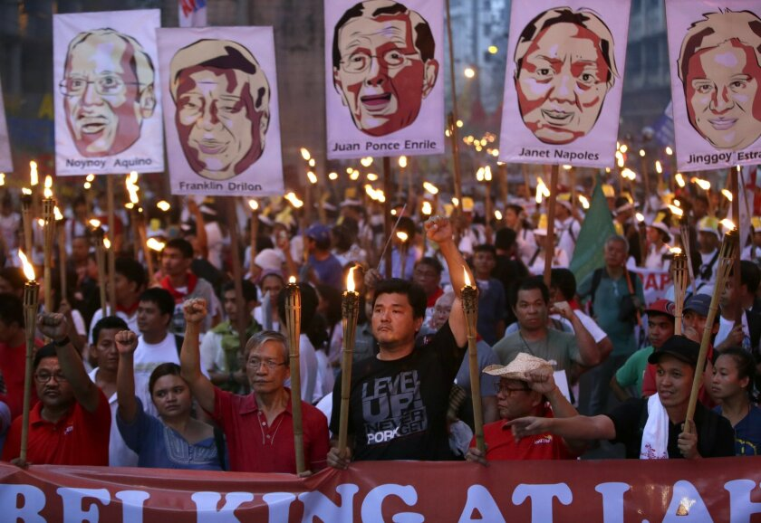 Carrying lighted torches, hundreds of activists march towards the Presidential Palace in Manila to demand that Philippine President Benigno Aquino III prosecute all officials, including some of his allies, who were allegedly involved in stealing from state funds intended for projects to help the poor Thursday, June 12, 2014, in the Philippines. Three senators and several of their associates have been charged with plunder for allegedly receiving hundreds of millions of pesos (millions of dollars) in kickbacks from a businesswoman who skimmed from the money off government allocations for the poor.(AP Photo/Bullit Marquez)