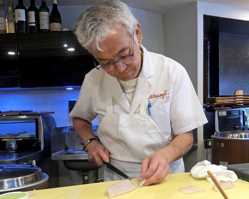 Chef Shunji Nakao behind the sushi counter at Shunji
