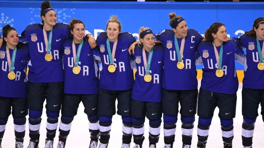 U.S. women's hockey celebrate during the victory ceremony after defeating Canada in a shootout in the Women's Gold Medal Game on Thursday.