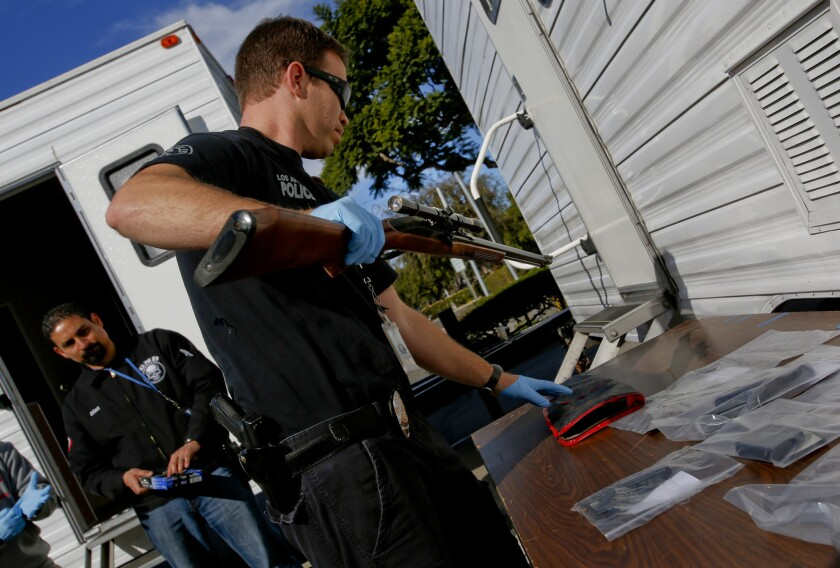 An officer unpacks a gun at a news conference where authorities announced the arrests of 19 alleged MS-13 members or associates.